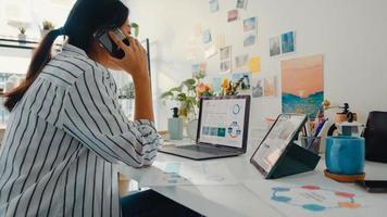 jovem mulher de negócios da Ásia ligar para o telefone móvel com colegas da empresa sobre o plano de mercado do gráfico de gráfico de finanças do trabalho no laptop e tablet em casa. aluna aprender online, trabalhar a partir do conceito de casa. foto