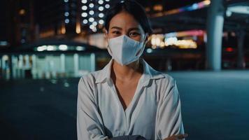 bem sucedida jovem empresária asiática em roupas de escritório de moda usar máscara médica sorrindo e olhando para a câmera enquanto feliz autônomo ao ar livre na noite urbana moderna da cidade. conceito de negócios em movimento. foto