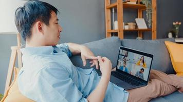 jovem empresário asiático usando laptop fala com colegas sobre o plano de uma reunião de videochamada enquanto trabalha em casa na sala de estar. auto-isolamento, distanciamento social, quarentena para prevenção do vírus corona. foto