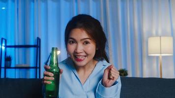 jovem senhora asiática bebendo cerveja se divertindo momento feliz noite festa evento on-line celebração via videochamada na sala de estar em casa. distanciamento social, quarentena para coronavírus. ponto de vista ou pov. foto