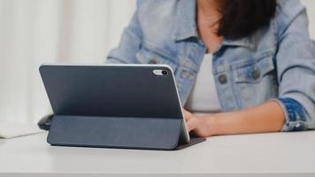 retrato de freelance smart business mulheres casual wear usando tablet trabalhando no local de trabalho, sala de estar em casa. feliz jovem asiática relaxar sentado na mesa de pesquisa e trabalhar na internet. foto