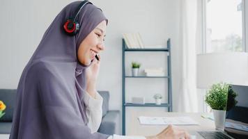 ásia senhora muçulmana usar fone de ouvido assistir webinar ouvir curso on-line comunicar-se por videoconferência em casa. trabalho remoto de casa, distanciamento social, quarentena para prevenção do vírus corona. foto