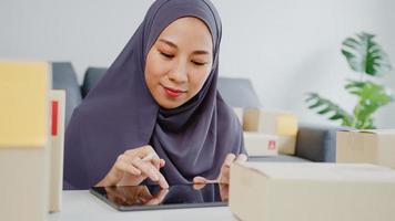 jovem empresária muçulmana da ásia verifica o pedido de compra do produto em estoque e economiza no trabalho do computador tablet no escritório em casa. proprietário de uma pequena empresa, entrega de mercado online, conceito freelance de estilo de vida. foto
