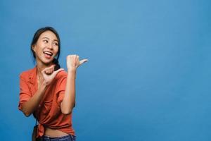 retrato de uma jovem senhora asiática, sorrindo com uma expressão alegre, mostra algo incrível no espaço em branco em roupas casuais e em pé isolado sobre um fundo azul. conceito de expressão facial. foto