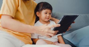 feliz alegre mãe de família asiática e filho bonito usando desenho animado digital tablet interesse e assistir filme se divertindo, relaxe no sofá na sala de estar em casa. passar um tempo juntos, quarentena para coronavírus. foto