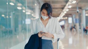 garota de negócios asiáticos usar telefone inteligente para o check-in do cartão de embarque a pé com a bagagem para o terminal de voo doméstico no aeroporto. pandemia de covid de viajante de negócios, conceito de distanciamento social de viagens de negócios. foto