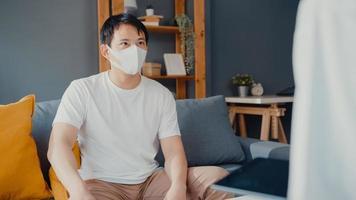 jovem médica médica asiática usa máscara facial usando tablet digital, compartilhando boas notícias de testes de saúde com paciente masculino feliz sentado no sofá em casa. seguro médico, visite o conceito de paciente em casa. foto
