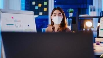ásia empresária usa máscara facial para distanciamento social no novo normal para apresentação de prevenção de vírus com um colega sobre o plano de videochamada enquanto trabalha no escritório à noite. estilo de vida após o coronavírus. foto