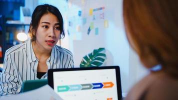 grupo de empresários da Ásia usando apresentação de computador laptop e reunião de comunicação de brainstorming de idéias sobre novos colegas de projeto, estratégia de sucesso de plano de trabalho no escritório em casa moderno à noite. foto