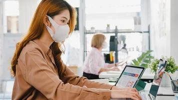ásia empresária empresária usando máscara médica para distanciamento social em uma nova situação normal para prevenção de vírus enquanto usa o laptop no trabalho no escritório. estilo de vida após o vírus corona. foto