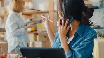 jovens empresárias da ásia usando telefone celular para receber o pedido de compra e verificar o produto no estoque trabalham no escritório em casa. proprietário de uma pequena empresa, entrega de mercado online, conceito freelance de estilo de vida. foto