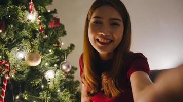 jovem asiática usando videochamada de telefone inteligente falando com o casal, árvore de Natal decorada com enfeites na sala de estar em casa. distanciamento social, noite de natal e festival de feriado de ano novo. foto