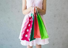 linda mulher segurando um saco de papel para comprar roupas foto