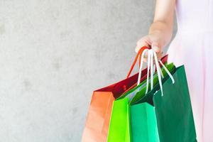 close-up da mão de uma mulher segurando sacolas de compras. foto