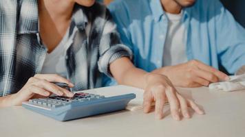 O homem e a mulher do casal asiático de estresse usam a calculadora para calcular o orçamento familiar, as dívidas, as despesas mensais durante a crise econômica financeira em casa. problemas de dinheiro do casamento, conceito de planejamento de orçamento familiar. foto