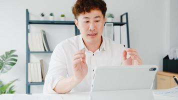 jovem empresário asiático usando tablet conversa com colegas sobre o plano de videochamada enquanto inteligente trabalhando em casa na sala de estar. auto-isolamento, distanciamento social, quarentena para prevenção do vírus corona. foto