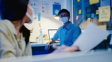 Feliz empresária asiática usa máscara para distanciamento social em uma nova situação normal para prevenção de vírus, enquanto discute o brainstorm de negócios, reunião para compartilhar dados no trabalho à noite no escritório foto
