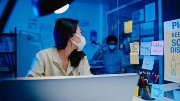 empresário asiático desligue o computador e diga adeus ao colega que ainda está trabalhando quando ele saiu do trabalho depois de terminar as horas extras na noite de um pequeno escritório em casa moderno. conceito de parceria de colega de trabalho. foto