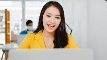 Ásia empresária distanciamento social em nova situação normal para prevenção de vírus ao usar laptop apresentação para colegas sobre plano em videochamada enquanto trabalha no escritório. vida após o vírus corona. foto