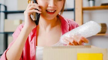 jovem empresária da ásia usando telefone celular para receber o pedido de compra e verificar o produto em estoque, trabalhar no escritório em casa. proprietário de uma pequena empresa, entrega de mercado online, conceito freelance de estilo de vida. foto