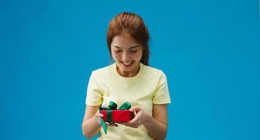 jovem asiática sorrir e receber a caixa de presente isolada sobre o fundo azul. copie o espaço para colocar um texto, mensagem para anúncio. área de publicidade, maquete de conteúdo promocional. foto