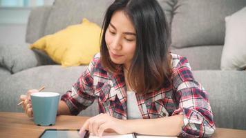 mulher estudante asiática fazer lição de casa em casa, mulher bebendo café e usando o tablet para pesquisar no sofá na sala de estar em casa. mulheres de estilo de vida relaxam no conceito de casa. foto