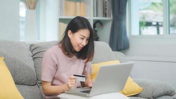 mulher asiática usando laptop e comércio eletrônico de compras com cartão de crédito, mulher relaxa se sentindo feliz compras on-line, sentado no sofá na sala de estar em casa. mulheres de estilo de vida relaxam no conceito de casa. foto