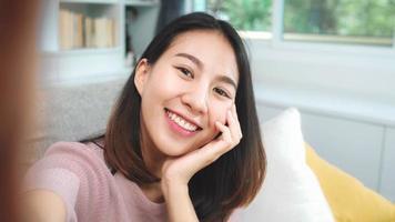 jovem adolescente asiático mulher vlog em casa, mulher usando smartphone, fazendo vídeo vlog para mídias sociais na sala de estar. mulher de estilo de vida relaxa no conceito de manhã em casa. foto