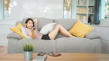 mulher jovem adolescente asiático assistindo tv em casa, sentindo-se feliz feminino deitado no sofá na sala de estar. mulher de estilo de vida relaxa no conceito de manhã em casa. foto