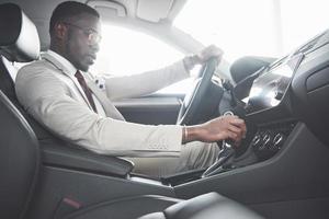 elegante empresário negro sentado ao volante de um carro de luxo. homem afro-americano rico foto
