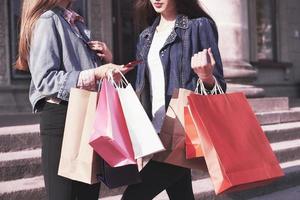 duas jovens carregando sacolas de compras enquanto caminha pela rua após visitar as lojas foto