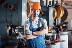 retrato de um jovem trabalhador em um capacete em uma grande usina de metais. shiftman no armazém de produtos acabados foto