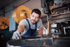 operador experiente em um capacete. conceito da indústria metalúrgica engenheiro profissional metalúrgico operando centro de fresadora cnc na oficina de manufatura foto