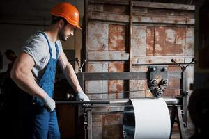 retrato de um jovem trabalhador em um capacete em uma grande usina de metais. o engenheiro atende as máquinas e fabrica peças para equipamentos de gás foto