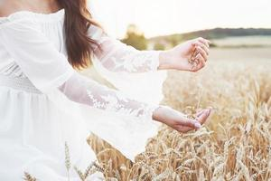 linda garota em um campo de trigo em um vestido branco, uma imagem perfeita no estilo de vida foto