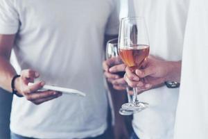 velhos amigos alegres comunicam-se uns com os outros e assistem ao telefone, com copos de uísque ou vinho no bar. conceito de entretenimento e estilo de vida. pessoas conectadas por wi-fi em reunião de mesa de bar foto