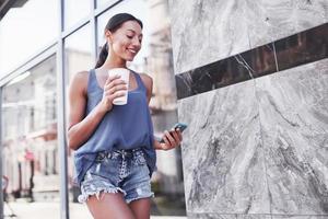 retrato de uma mulher jovem e elegante hippie andando na rua, vestindo uma roupa da moda fofa, bebendo café com leite quente e sorrindo foto