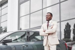 visitando concessionária de automóveis. homem de negócios preto casual de terno perto do carro foto