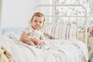 conceito de infância. menina com vestido bonito localização na cama brincando com brinquedos em casa. quarto infantil branco vintage foto
