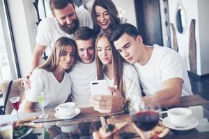 um grupo de pessoas tira uma foto de selfie em um café. os melhores amigos reunidos em uma mesa de jantar comendo pizza e cantando vários drinks