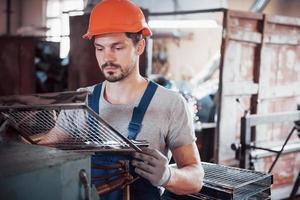 retrato de um jovem trabalhador em um capacete em uma grande fábrica de reciclagem de resíduos. o engenheiro monitora o trabalho de máquinas e outros equipamentos foto