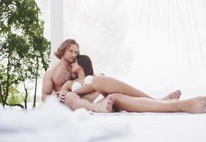um lindo casal relaxando na praia, vestindo roupa de banho. atmosfera romântica foto