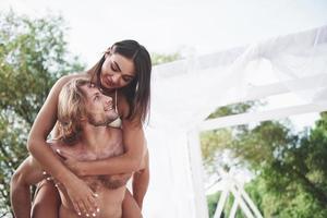 jovem feliz vestindo sua esposa nos ombros da praia foto