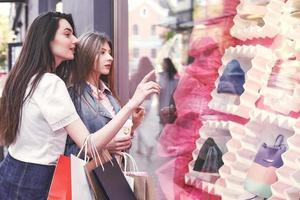 mulher feliz com sacolas de compras apontando o dedo na vitrine foto