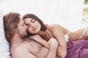 um lindo casal relaxando na praia, vestindo roupa de banho. atmosfera romântica. foto