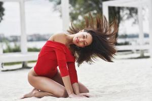 uma garota sexy em um maiô vermelho posa para o fotógrafo. linda morena com cabelos longos relaxando na praia. foto
