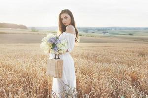 linda garota de vestido branco correndo no campo de trigo de outono ao pôr do sol foto