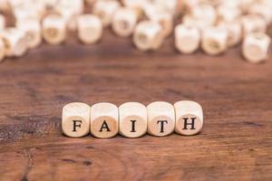 cubos de madeira com mesa de palavra fé foto