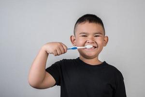 garotinho escovando os dentes em foto de estúdio