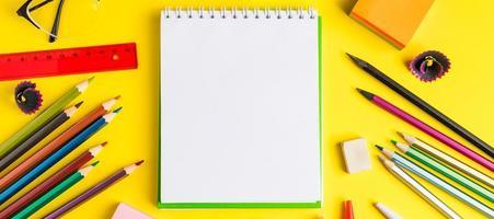 postura plana de artigos de papelaria em fundo amarelo. de volta ao conceito de escola. lugar para texto. foto